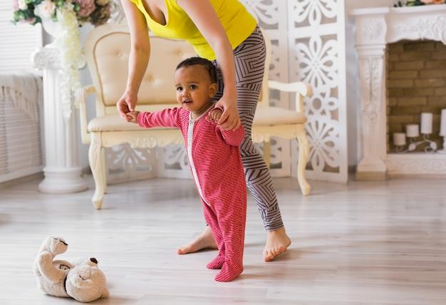 Słodkie małe dziecko rasy mieszanej uczy się chodzić, mama trzyma jego ręce