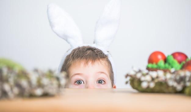 Słodkie małe dziecko sobie uszy królika na wielkanoc. chłopiec trzyma malowane jajka na białym tle.