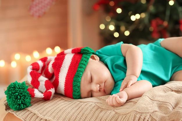 Słodkie małe dziecko śpiące przed niewyraźnymi lampkami świątecznymi