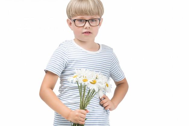 Słodkie małe dziecko trzyma kwiaty. chłopiec z rumiankiem. urocze dziecko gratuluje mamie bukietu kwiatów. odosobniona chłopiec na białym tle.