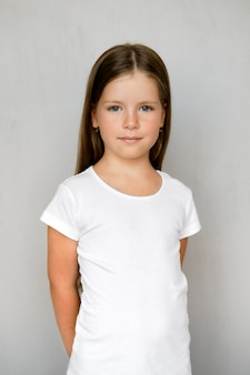 Słodkie małe dziecko z długimi włosami w biały t-shirt i czarne spodnie dresowe pozowanie