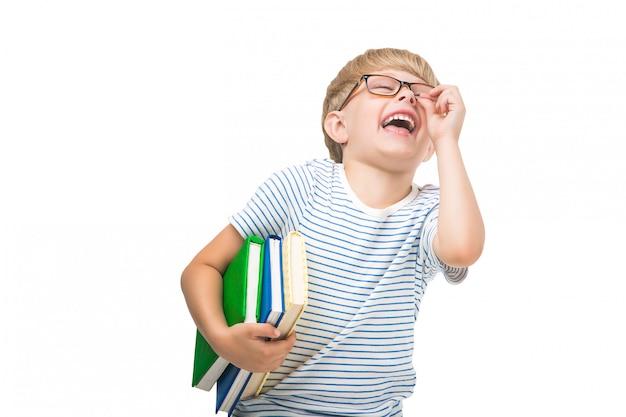 Słodkie małe dziecko z książek i zeszytów urocze dziecko czytanie. strzał studio uczniak. chłopiec w okularach.
