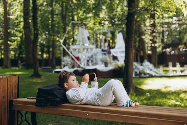 Słodkie małe europejskie dziecko skupione na smartfonie na ławce w parku