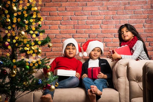 Słodkie małe indyjskie azjatyckie dzieci świętujące boże narodzenie w domu z czapką świętego mikołaja, prezentami i choinką