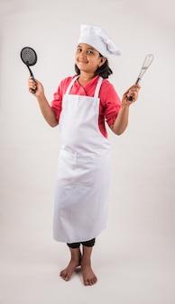 Słodkie małe indyjskie dziecko lub dziewczynka przebrana za szefa kuchni i trzymająca naczynia do gotowania lub warzywa, stojąca na białym tle nad białym tłem