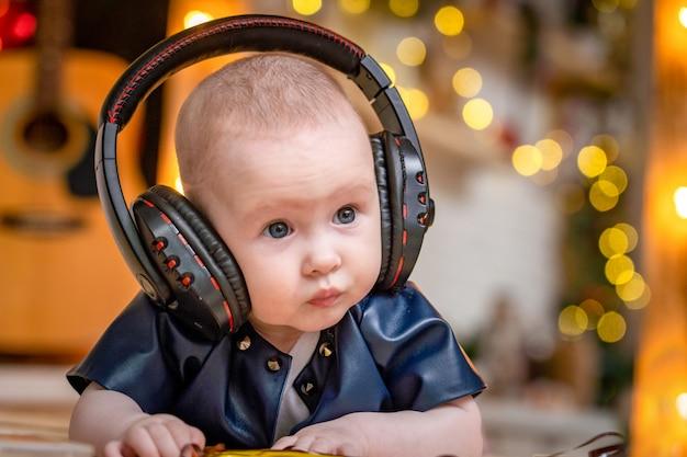 Słodkie maleństwo leży na brzuchu ze słuchawkami i słucha muzyki.