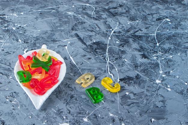 Słodkie marmolady w kształcie liter na marmurowym tle.