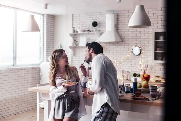 Słodkie momenty. dość długowłosa młoda kobieta ubrana w atłasową bluzkę karmiąca swojego męża