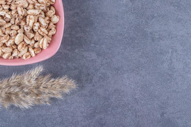 Słodkie musli w misce obok trawy pampasowej, na niebieskim stole.