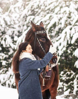 Słodkie nastolatka z koniem zimą w lesie. komunikowanie się ze zwierzętami. pionowy