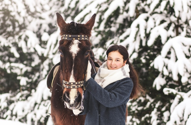 Słodkie nastolatka z koniem zimą w lesie. komunikowanie się ze zwierzętami