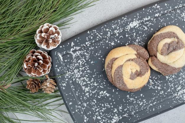Słodkie okrągłe ciasteczka na desce z szyszkami.