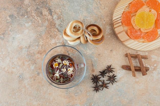 Słodkie okrągłe ciasteczka z herbatą ziołową i marmoladą