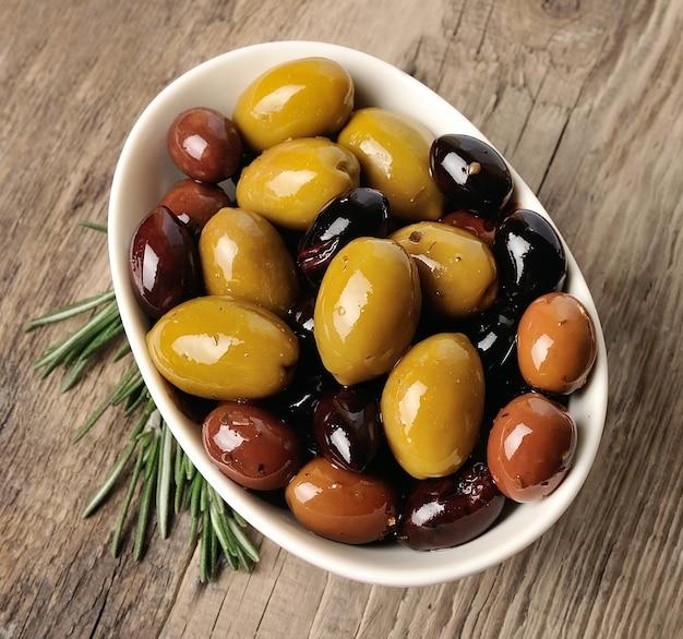 Słodkie oliwki z bliska na drewnianej teksturze. mieszanka oliwek.