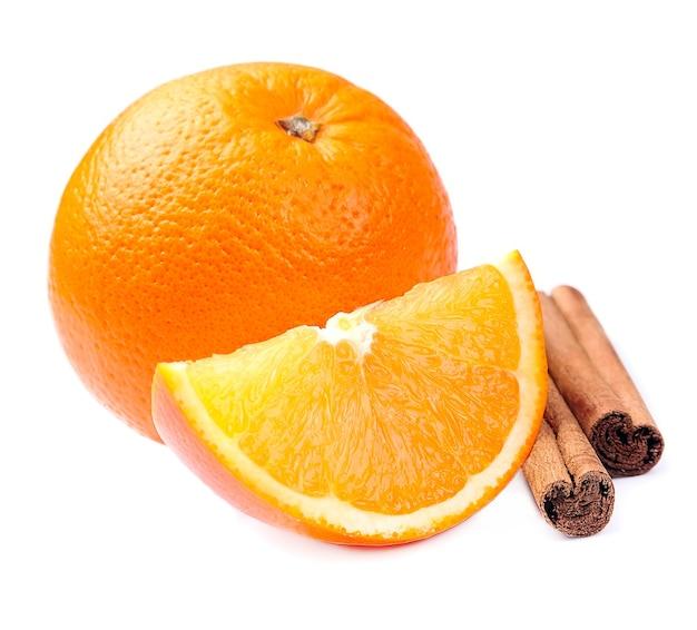 Słodkie owoce pomarańczy z cynamonem na białym tle