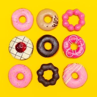 Słodkie pączki moda na żółtym tle. płaska sztuka minimalna fast food