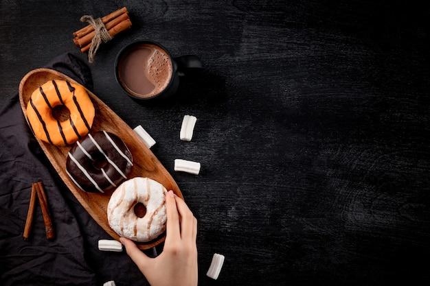 Słodkie pączki na talerzu i gorąca czekolada w kubku na czarno