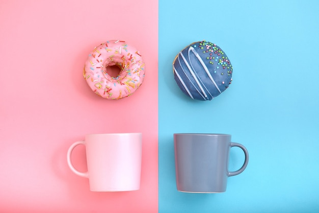 Słodkie pączki różowo-niebieskie z kubkiem kawy
