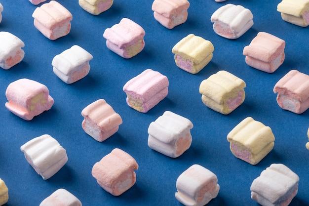 Słodkie pianki na niebieskim tle. koncepcja minimalizmu