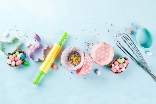 Słodkie pieczenie na wielkanoc, gotowanie z pieczeniem - z wałkiem do ciasta, trzepaczka do ubijania, foremki do ciastek, posypanie cukrem, mąka. jasnoniebieskie tło, widok z góry copyspace