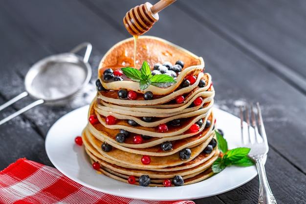 Słodkie pieczone domowe naleśniki z jagodami i miodem na pyszne śniadanie.