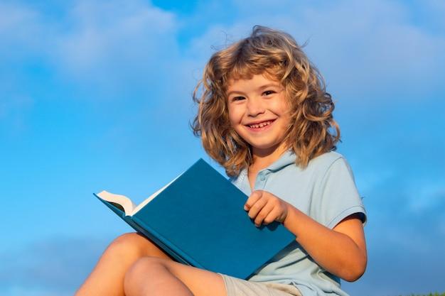 Słodkie piękne dziecko czytanie książki na tle błękitnego nieba na zewnątrz. dzieciak czytał książkę w parku.