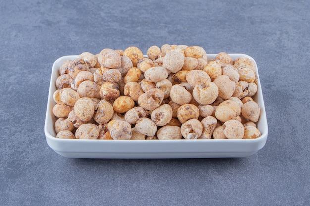 Słodkie płatki kukurydziane z musli w misce, na marmurowym stole.