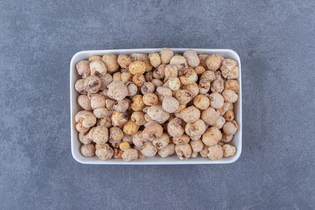 Słodkie płatki kukurydziane z musli w misce, na marmurowym tle. zdjęcie wysokiej jakości
