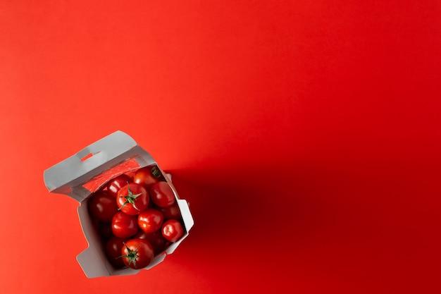 Słodkie pomidory czereśniowe w paparze wyjmują pudełko
