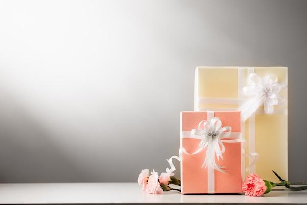 Słodkie pudełko i kwiat goździka w delikatnej tonacji kolorystycznej