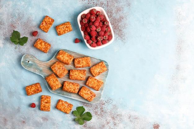 Słodkie pyszne ciasteczka z dżemem malinowym z dojrzałymi malinami, widok z góry