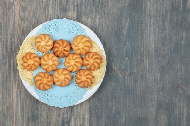 Słodkie pyszne rumiane kruche ciasteczka w białym talerzu