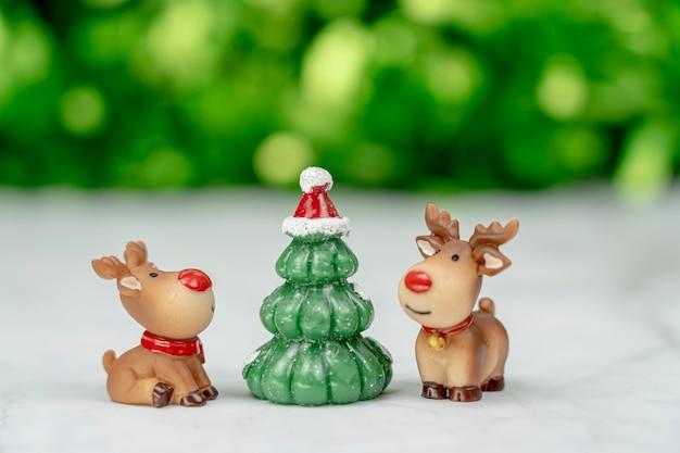 Słodkie renifery z choinką czekają na wesołe święta bożego narodzenia