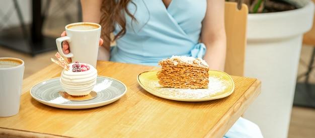 Słodkie różne kawałki ciasta na talerzach przy stole na tle kobiety przy filiżance kawy w kawiarni