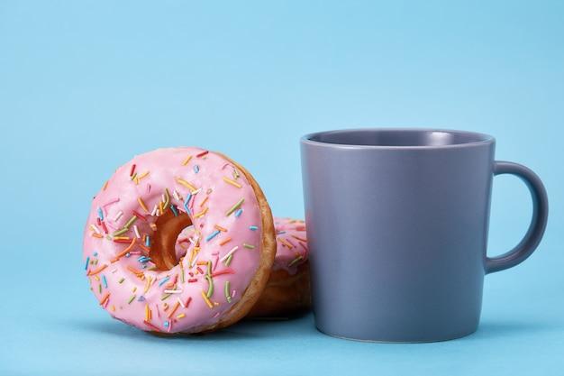 Słodkie różowe pączki z niebieskim kubkiem na niebieskim tle. deser koncepcyjny, słodkie życie, jesteśmy tym, co jemy. niebieskie tło, kopia przestrzeń.