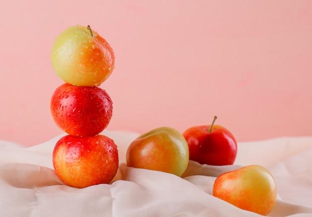 Słodkie śliwki na powierzchni tekstylnej i różowej