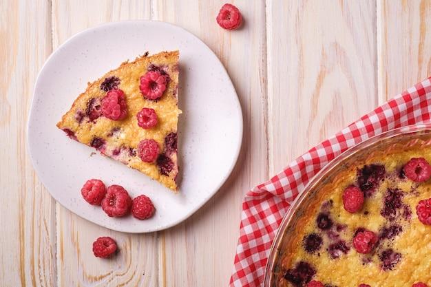 Słodkie, smaczne ciasto z galaretowatymi i świeżymi owocami malin w naczyniu do pieczenia i talerzu z czerwonym ręcznikiem obrusowym, drewniana powierzchnia stołu, widok z góry