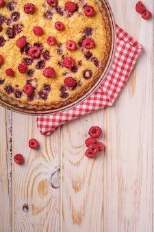 Słodkie smaczne ciasto z galaretowatymi i świeżymi owocami malin w naczyniu do pieczenia z czerwonym ręcznikiem obrusowym, drewniana powierzchnia stołu, widok z góry