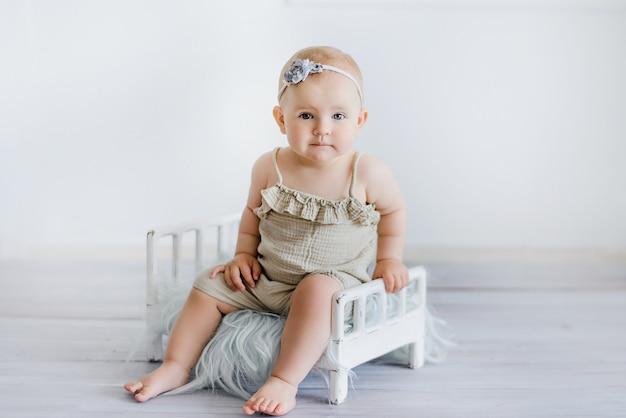Słodkie śmieszne dziecko na łóżku w pokoju dziecięcym. kartkę z życzeniami, miejsce na tekst. plakat na święta wielkanocne. gratulacje z okazji dnia matki. cute dziewczynka 6 miesięcy siedzi i czołga się.