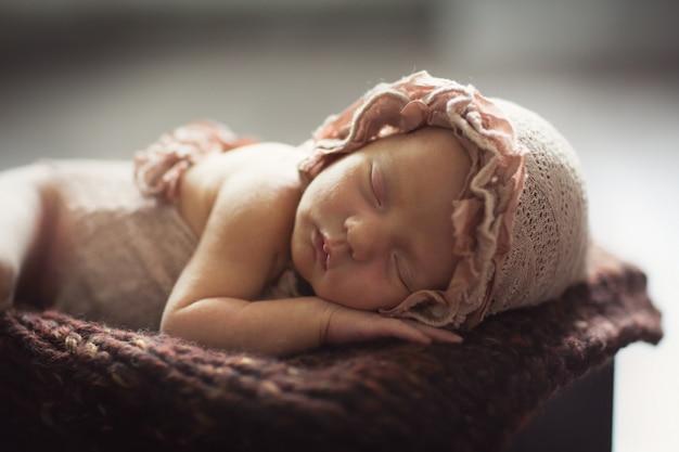 Słodkie śpiące leniwe dziecko w pudełku, ciemny styl