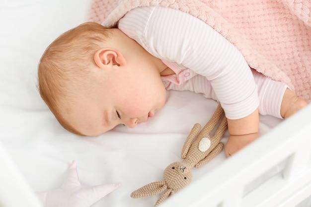 Słodkie śpiące małe dziecko w łóżku