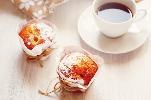 Słodkie świeże pieczone babeczki z filiżanką kawy