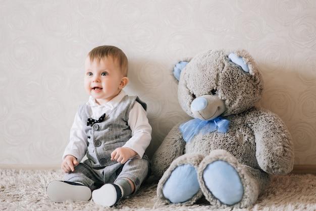 Słodkie szczęśliwe dziecko w stylowym stroju dżentelmena siedzi na białym dywanie i bawi się swoim misiem, śmiejąc się z niego.