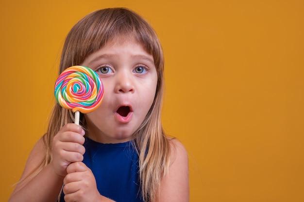 Słodkie szczęśliwe dziecko z candy lollipop, szczęśliwa dziewczyna je duży cukier lizaka, dziecko jeść słodycze. zdziwione dziecko z cukierkami. na białym tle na żółtym tle, studio. piękna mała dziewczynka z lizakiem