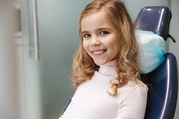 Słodkie szczęśliwe piękne dziecko dziewczyna siedzi w centrum medycznego dentysty patrząc na kamery.