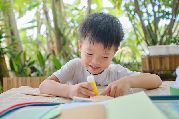 Słodkie, szczęśliwe uśmiechnięte azjatyckie dziecko w wieku przedszkolnym lubi używać kleju, robiąc sztukę w domu, zabawne rzemiosło z papieru i kleju dla małych dzieci, projekt artystyczny dla dzieci, zabawki diy dla dzieci, koncepcja nauczania domowego