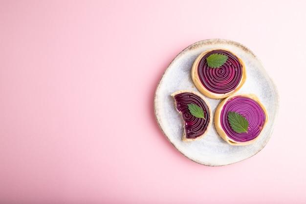 Słodkie tartaletki z galaretką i kremem mlecznym na pastelowym różowym tle. widok z góry, płaski układ, miejsce na kopię.