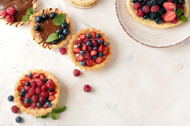 Słodkie tartaletki z jagodami na podświetlanym stole
