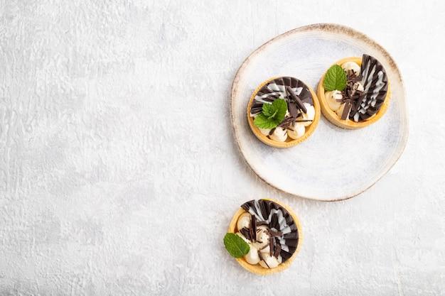 Słodkie tartaletki z kremem czekoladowym i serowym na szarym tle betonu. widok z góry, płaski układ, miejsce na kopię.