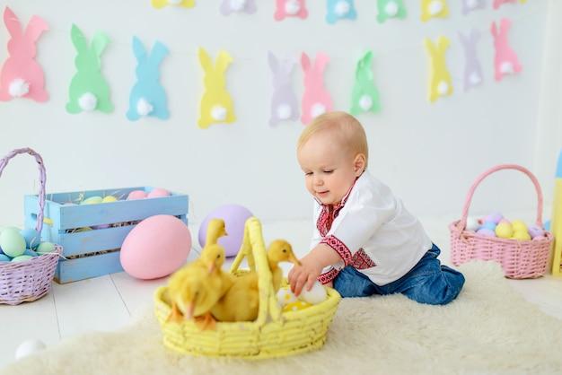 Słodkie uśmiechnięte dziecko w tradycyjny haft w kolorowe ozdoby wielkanocne